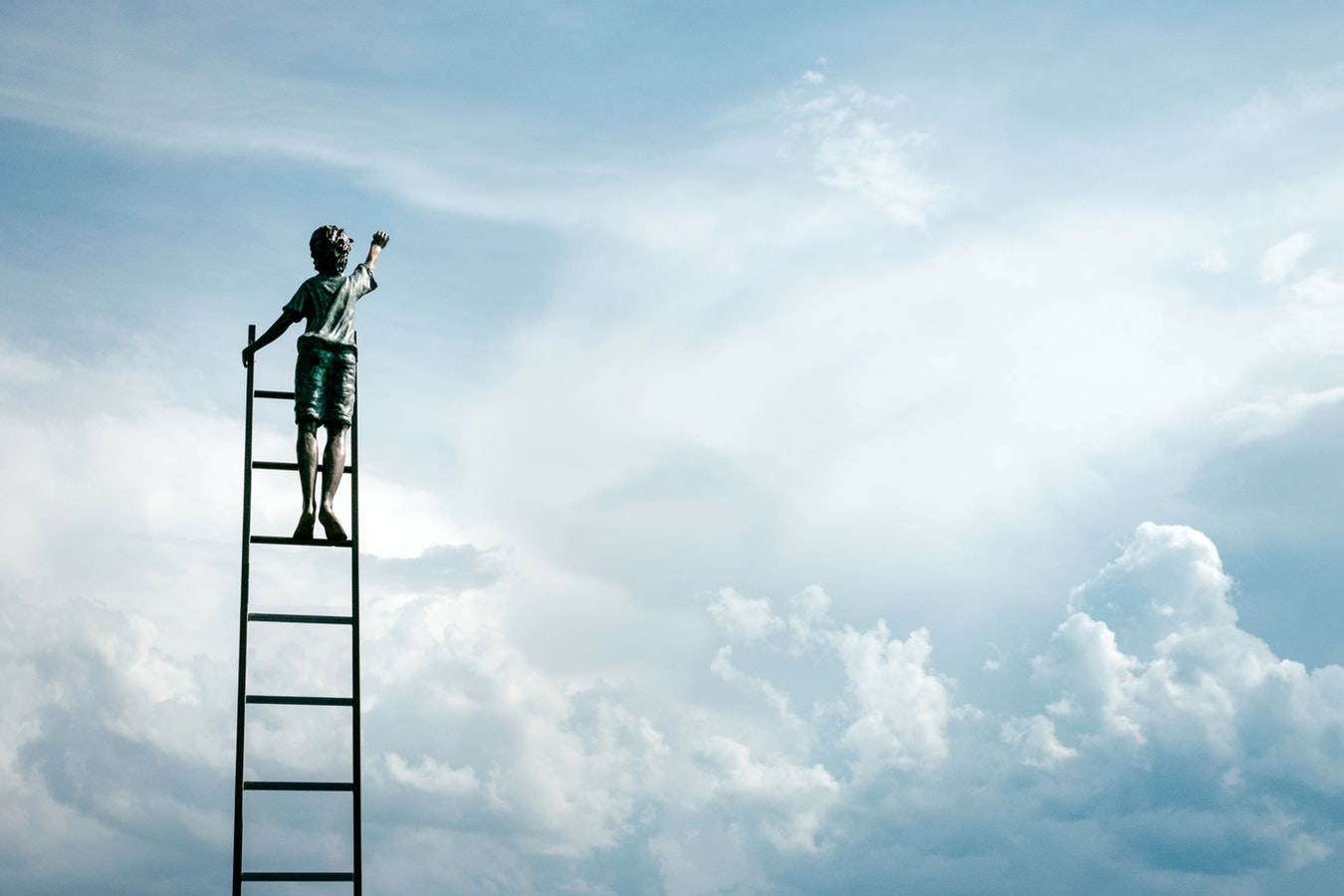 Image of a boy on a ladder reaching for the sky